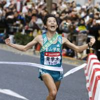 Aoyama Gakuin anchor Toshinori Watanabe crosses the finish line as his school becomes the first in 39 years to complete a wire-to-wire victory in the Hakone Ekiden on Sunday. Aoyama Gakuin won the title for the second consecutive year. | KYODO