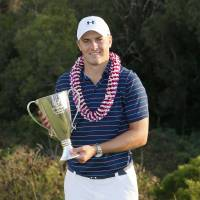 Jordan Spieth poses with the winner's trophy on Sunday in Kapalua, Hawaii. | AP