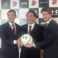 Dome Corporation president Shuichi Yasuda (center) poses for photographs with Iwaki FC president Satoshi Okura (left) and manager Pieter Huistra during a news conference on Wednesday in Tokyo. | JASON COSKREY