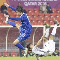 Yuta Toyokawa (right) attempts an acrobatic shot during Japan's 4-0 win over Thailand in Doha on Saturday. | KYODO