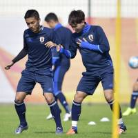 Japan Under-23s Yuya Kubo (left) and Takumi Minamino take part in a training session in Doha on Monday. | KYODO