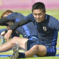 Yuya Kubo stretches in training ahead of Japan's Under-23 Asian Championship quarterfinal against Iran in Doha on Friday. | KYODO
