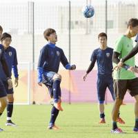 Takumi Minamino (center) controls the ball in training with Japan's Under-23s in Doha ahead of Tuesday's Under-23 Asian Championship semifinal against Iraq. | KYODO