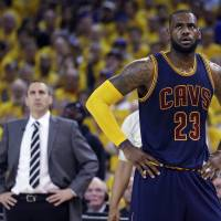 Cleveland's LeBron James stands on the court as then-coach David Blatt watches on during Game 2 of the NBA Finals in June 2015. | AP
