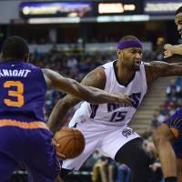 Kings center DeMarcus Cousins (center) dribbles to the basket while being defended by the Suns' T.J. Warren (right) and Brandon Knight during their game on Saturday in Sacramento, California. | USA TODAY / REUTERS