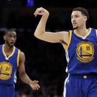 Warriors guard Klay Thompson celebrates a basket as teammate Ian Clark (left) looks on during the first half of their game on Tuesday in Los Angeles. The Warriors beat the Lakers 109-88. | AP