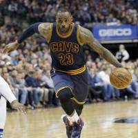 Cleveland's LeBron James drives to the basket during the Cavaliers' 110-107 win over the Mavericks in Dallas on Tuesday. | AP