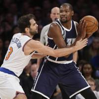 Oklahoma City's Kevin Durant (right) keeps the ball away from New York's Jose Calderon during the Thunder's 128-122 win over the Knicks on Tuesday. | AP
