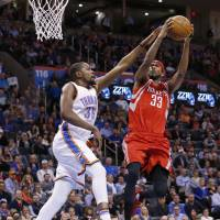 Oklahoma City's Kevin Durant defends as Houston's Corey Brewer goes up for a shot in the second quarter on Friday night. The Thunder beat the Rockets 116-108. | AP