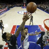 The Warriors' Brandon Rush (left) and the Sixers' Jahlil Okafor compete for a rebound during their game on Saturday in Philadelphia.   AP