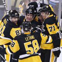 The Penguins' Sidney Crosby (center) is surrounded by his teammates after scoring against the Islanders on Saturday. | AP