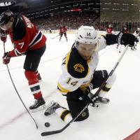 New Jersey's Jon Merrill (left) and Boston's Brett Connolly vie for the puck in the first period on Friday night. The Bruins beat the Devils 4-1. | AP