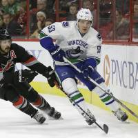 Carolina's Justin Faulk (left) and Vancouver's Bo Horvat vie for the puck in the first period on Friday night. The Canucks downed the Hurricanes 3-2 in overtime. | AP