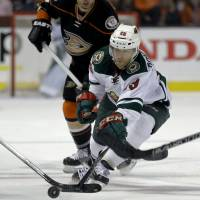 Minnesota's Jason Pominville (right) moves for the puck as Anaheim's Andrew Cogliano looks on Wednesday night. The Ducks beat the Wild 3-1. | AP