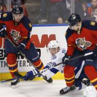 The Panthers' Reilly Smith (left) and Alex Petrovic (right) vie for the puck with the Lightning's Ondrej Palat on Saturday.   AP