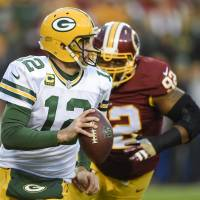 The Packers' Aaron Rodgers scrambles under pressure from Redskins defensive end Chris Baker on Sunday. | AP