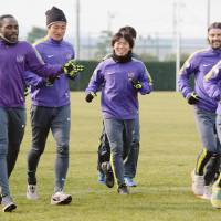 Striker Hisato Sato (center) shares a joke with his Sanfrecce Hiroshima teammates in training on Thursday. | KYODO