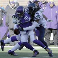 Seahawks cornerback Richard Sherman (right) breaks up a pass intended for Vikings receiver Adam Thielen during the first half on Sunday in Minnesota. | AP