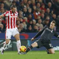 Liverpool's Lucas Leiva (right) battles Stoke's Erik Pieters for control of the ball during the first leg of their League Cup semifinal on Tuesday in Stoke, England. | REUTERS