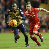 Arsenal's Joel Campbell (left) vies for the ball with Liverpool's Alberto Moreno in Premier League action on Wednesday night at Anfield. The match ended in a 3-3 draw. | REUTERS