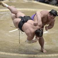 Shohozan throws Harumafuji to the ground on the second day of the New Year Grand Sumo Tournament on Monday. | KYODO