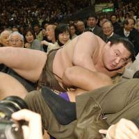 Hakuho falls into the crowd during the third day of the New Year Grand Sumo Tournament on Tuesday. | KYODO