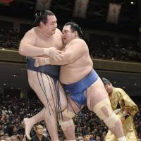 Kotoshogiku (right) grapples with yokozuna Kakuryu during the New Year Grand Sumo Tournament on Tuesday. | KYODO