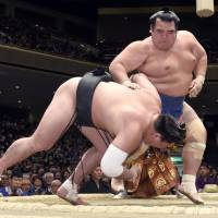 Kotoshogiku (right) sends Harumafuji to the ground at the New Year Grand Sumo Tournament on Thursday. | KYODO
