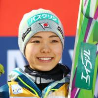 Sara Takanashi smiles from the podium after winning a World Cup ski jumping event on Sunday in Oberstdorf, Germany. | AP