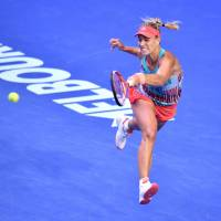 Angelique Kerber hits a return against Serena Williams during the Australian Open final on Saturday in Melbourne, Australia. Kerber defeated Williams 6-4, 3-6, 6-4. | AFP-JIJI