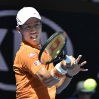Kei Nishikori hits a shot against Philipp Kohlschreiber during the first round of the Australian Open on Monday. Nishikori won 6-4, 6-3, 6-3. | KYODO