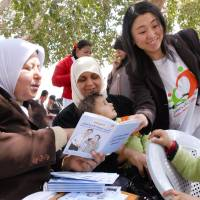 A Japan International Cooperation Agency volunteer shows a health handbook created for pregnant women and children to a woman in Palestine. | JICA