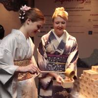 Kimono-clad women pour sake into masu (square wooden cup) with hishaku (bamboo ladle). | JAPAN NIGHT ORGANIZATION COMMITTEE