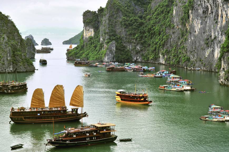 Junks sail around Ha Long Bay among spectacular karst formations and isles.