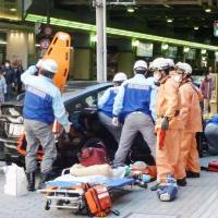 Ambulance staff rush to the scene where a car mowed down pedestrians on a sidewalk in the Umeda district of Osaka on Thursday. | KYODO
