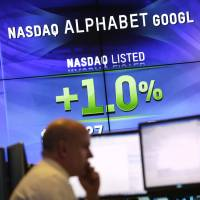 Electronic screens post the price of Alphabet stock on Monday at the Nasdaq MarketSite in New York. | AP