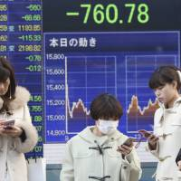 People pause in front of a stock price display showing the Nikkei's first close below 15,000 in 16 months.   AP
