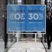 A man using his mobile phone walks past a sales advertisement board outside a cloth retailing store at a shopping district in Tokyo on Thursday. The nation's core consumer prices were unchanged in January from a year earlier. | REUTERS