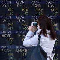 A woman uses her smartphone to take pictures of an electric quotation board flashing share prices of the Tokyo Stock Exchange in front of a securities company in Tokyo on Feb. 10. Tokyo stocks again dropped on Feb. 10 to their lowest level since late 2014, as fears of a global recession hammered investor confidence ahead of testimony by the head of the U.S. central bank. | AFP-JIJI