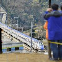 Railway fans watch a Hokuriku bullet train pass by in Tsubata-machi, central Ishikawa Prefecture, in March 2015. | KYODO