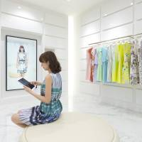 A customer simulates trying on clothes in a virtual changing room at Seiren Co.'s headquarters in Fukui Prefecture. | SEIREN CO.