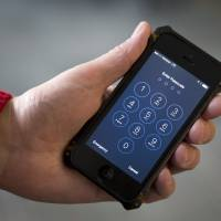 An iPhone is seen in Washington Feb. 17. The San Bernardino County-owned iPhone at the center of an unfolding high-profile legal battle between Apple Inc. and the U.S. government lacked a device management feature bought by the county that, if installed, would have allowed investigators easy and immediate access. | AP