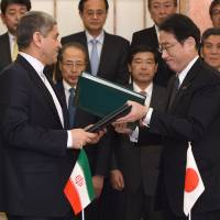 Foreign Minister Fumio Kishida (right) and Iranian Economic and Finance Minister Ali Taiebnia (left) exchange documents during a signing ceremony for an investment agreement in front of Japanese and Iranian business representatives at the Foreign Ministry in Tokyo on Friday. | AFP-JIJI
