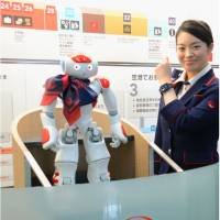 A humanoid robot guide, Nao, seen at Haneda airport on Tuesday, offers information about departures and the weather. | JAPAN AIRLINES CO. / KYODO