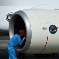 A maintenance worker inspects an engine on the Mitsubishi Regional Jet at Nagoya airport in Aichi Prefecture last November. | BLOOMBERG