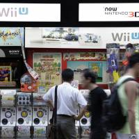 Pedestrians walk past signage advertising Nintendo products outside an electronics store in Tokyo. | BLOOMBERG