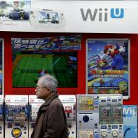A man stands in front of an advertisement for Nintendo's Wii U game console in Tokyo on Tuesday. Nintendo reported a 5.3 percent increase in third-quarter operating profit, in line with analysts forecasts, as lower costs helped offset a decline in overall sales. | REUTERS