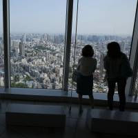 Tourists take in the view of Tokyo from the Roppongi Hills Mori Tower in Tokyo on May 9, 2014. Japan is gearing up for an influx of visitors ahead of the 2020 Games. | AP