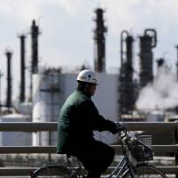 A worker cycles near a factory located in the Keihin industrial zone in Kawasaki on Feb. 17. | REUTERS
