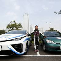Toyota Motor Corp. President Akio Toyoda stands between the Mirai fuel cell-powered vehicle (left) and a first-generation Prius hybrid vehicle ahead of the 44th Tokyo Motor Show last October. | BLOOMBERG